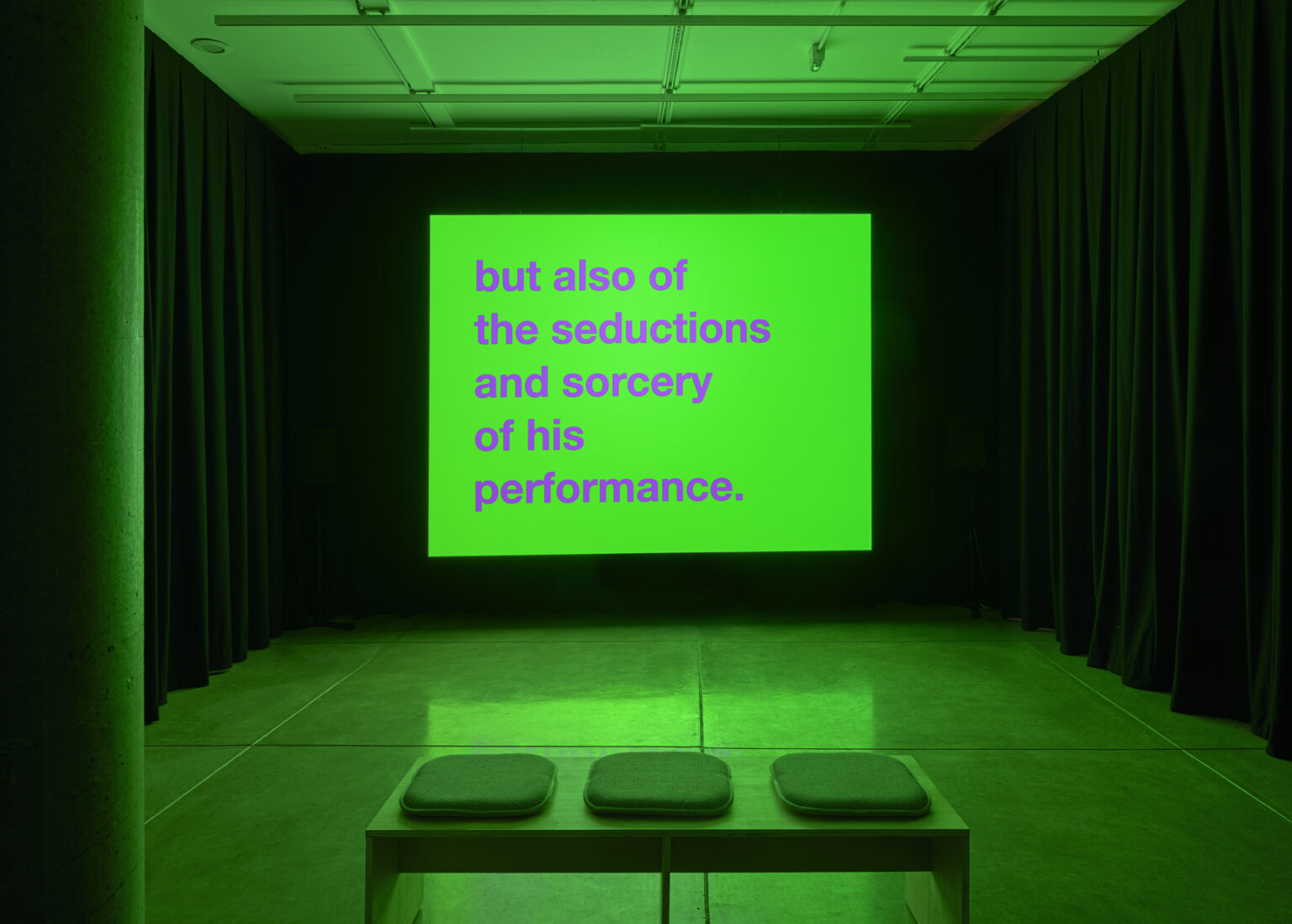 """room bathed in green light with a projection of """"but also if the seductions and sorcery of his performance."""""""