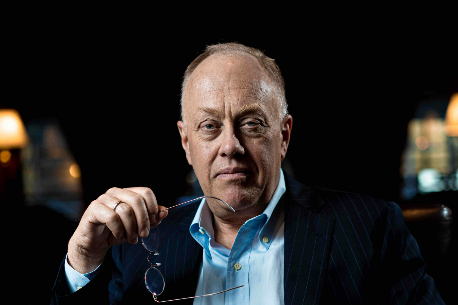 Head shot of author Chris Hedges seated holding his glasses